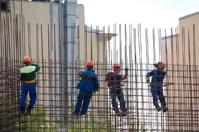 """Foto de trabalhadores montando armaduras de aço – Clique em """"Autorizar imagens"""" para ver."""