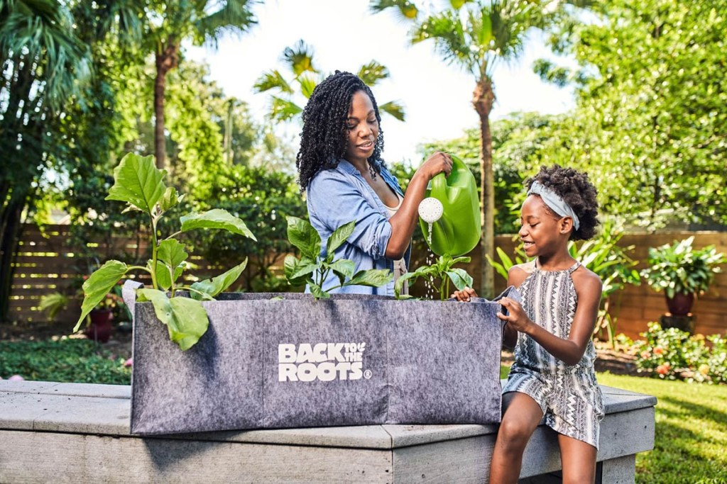 Mother and daughter watering their Back to the Roots Fabric Raised Garden Bed kit