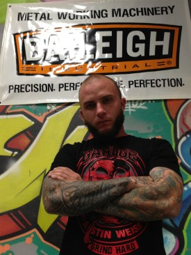 Austin Weiss stands in front of Baileigh Industrial Logo
