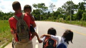 volunteering in Ecuador, a man and three children walking a long a road in Ecuador