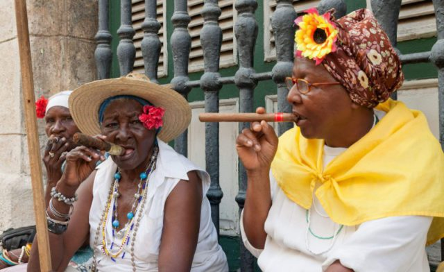 Elderly women with flowers in their hair, smoking cigars in Cuba