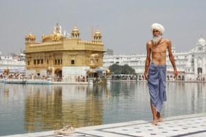 A shirtless older man in Harmandir Sahib