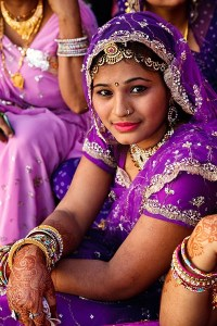 India Woman smiles at camera dressed in traditional garb