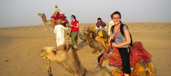 Woman smiling and camera while on a Camel Safari
