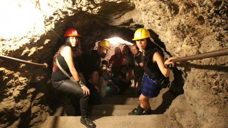 A group of people with helmets in a cave