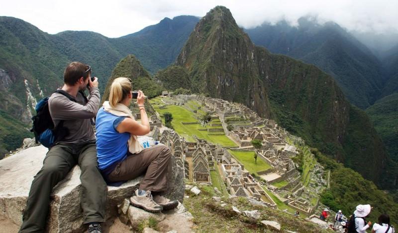 A couple taking photos of Machu Picchu