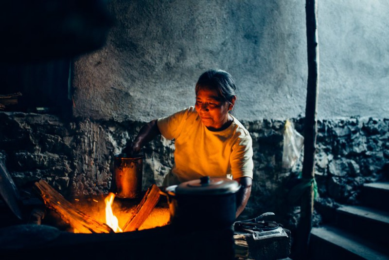 An elderly woman cooking with fire