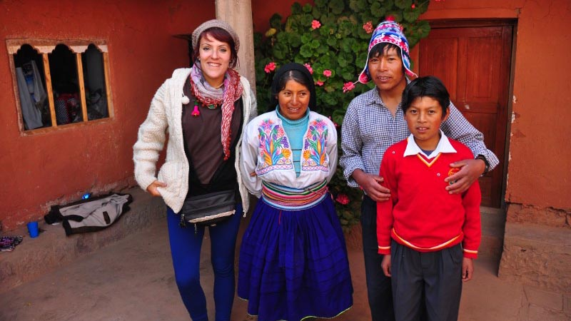 A smiling woman with her homestay family of three