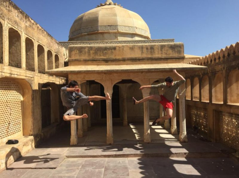 Making friends while traveling: Two friends doing a fun, silly ninja pose together