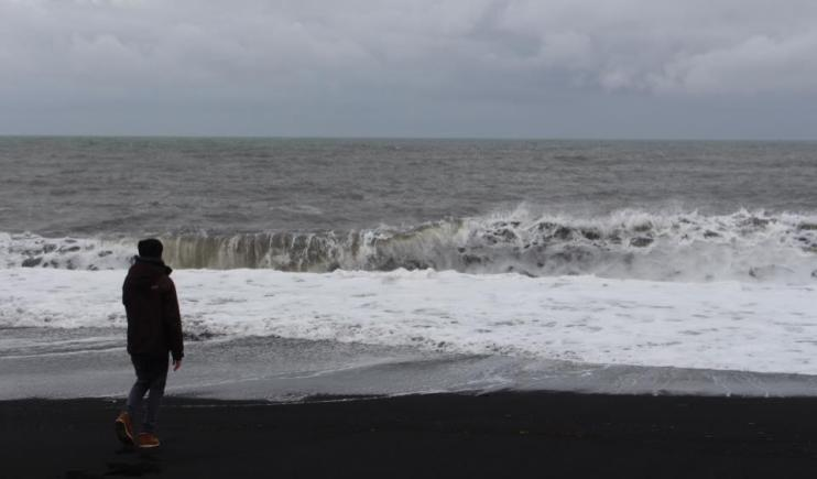 Watching the tide roll in at Black Sand Beach- 2 Weeks in Iceland
