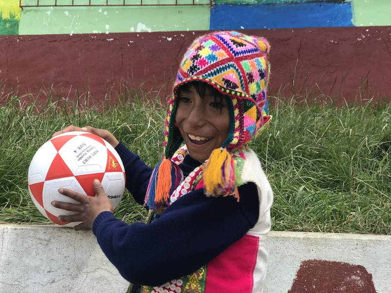 A small peruvian boy, wearing a colourful hat, smiles while holding a football