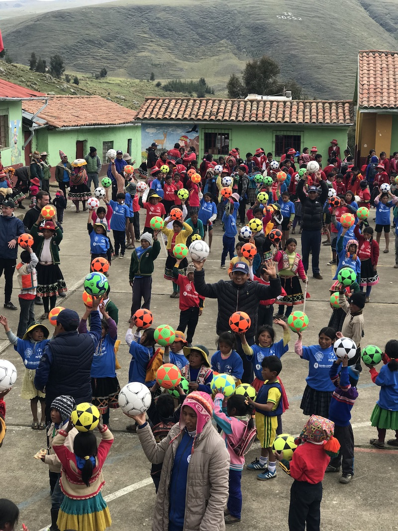 A large group a peruvian children with footballs given to them by Futbol for Kids