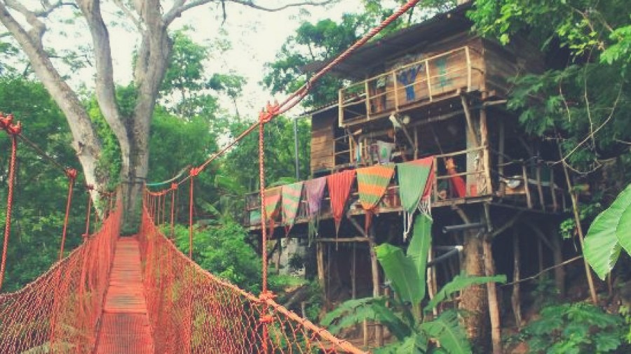 Red suspended bridge leading to wooden tree house, Nicaragua's treehouse Hostel
