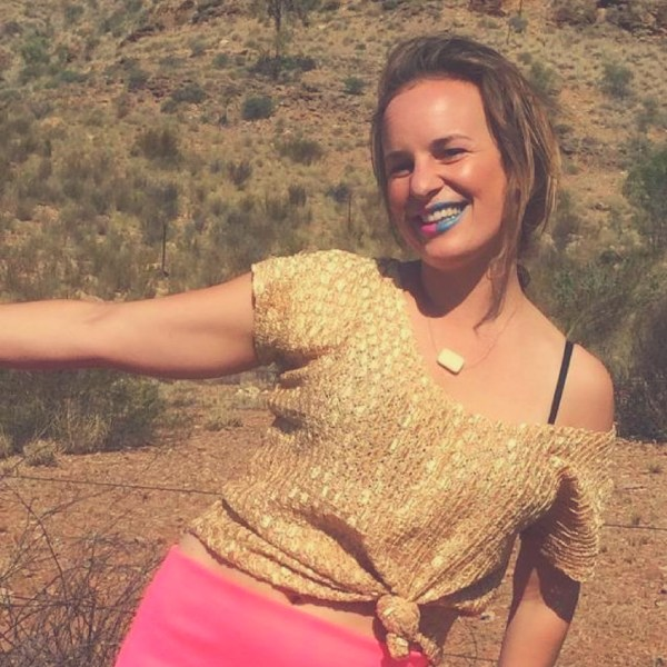 Smiling blonde woman with a gold shirt and blue and pink lipstick in the desert