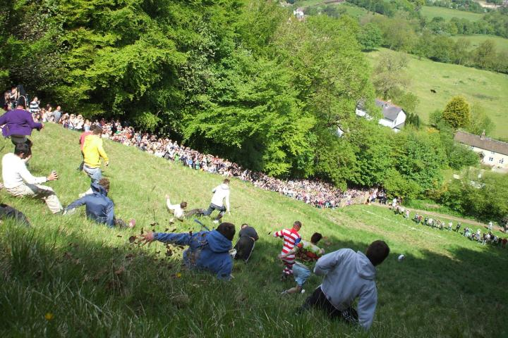 Competitors racing down a hill after a wheel of cheese at the Cooper's hill Cheese Rolling