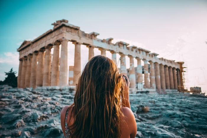 A woman with long hair, seen from behind, taking a photo of ruins in Greece
