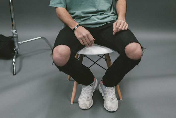 A man from the chest down, wearing ripped jeans and whit sneakers sitting on a white chair