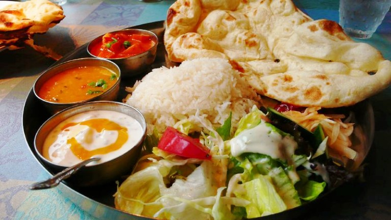 A mix plate of different Indian vegetarian dishes and flat bread