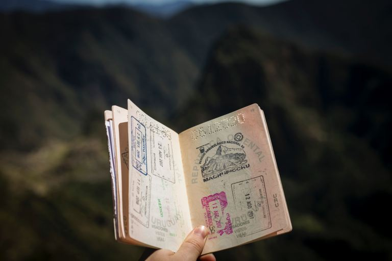 A person holding a passport full of stamps
