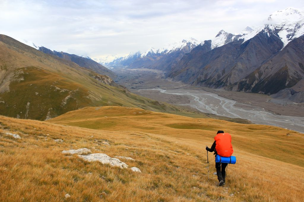 A man with a large red backpack hikes through the mountains in Kyrgyzstan
