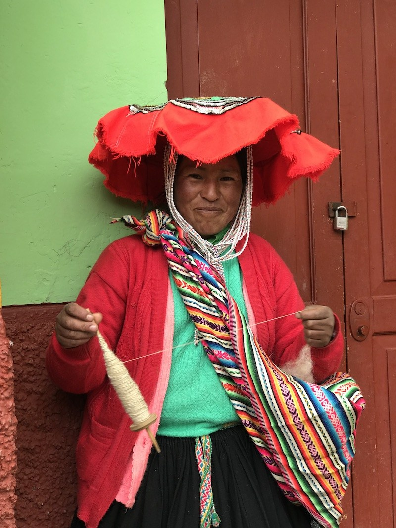 A Peruvian woman n colourful clothing weaving some thread