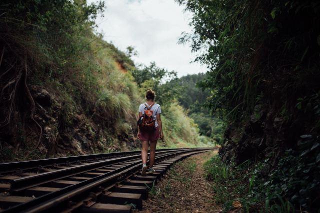 Girl walking alongtrain tracks on her way to Ella rock, Sri Lanka