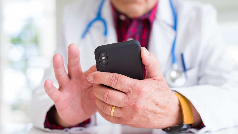 Close up of doctor man hands using smartphone and wearing stethoscope