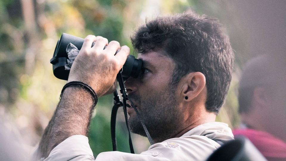 man using binoculars on safari