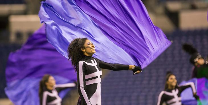 Pretty African-American color guard performer spinning a purple flag on an ultralite flag pole.