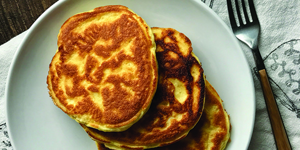 overhead photo of three high protein pancakes on a white plate