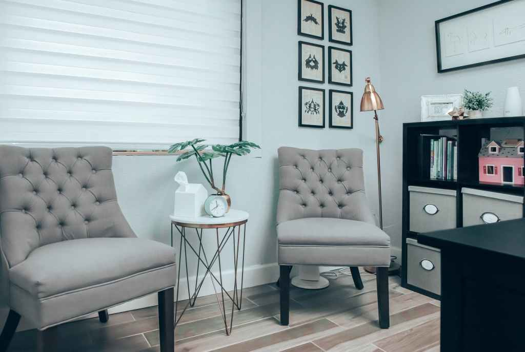gray chairs near white round table in psychotherapist office
