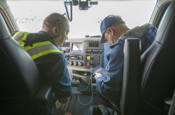 Man looking at a mobile device in the passenger seat, with truck driver looking over.
