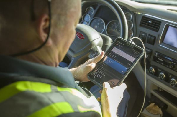 Truck driver looking at his mobile device and hours of service.