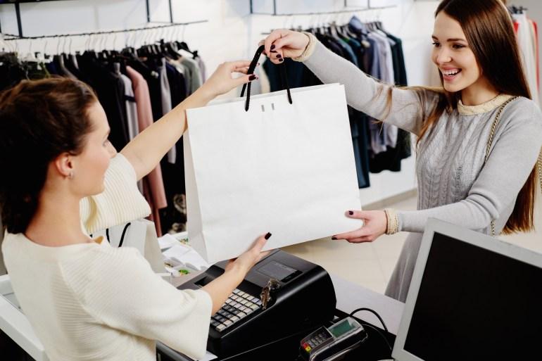 Vendedora entregando sacola de compras para cliente feliz