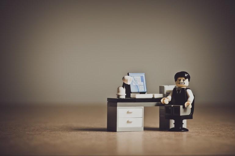 escritório com mesa e cadeira de brinquedo e um boneco triste, representando um empresário avaliando o churn