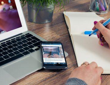 Escritório com mão feminina escrevendo em um papel