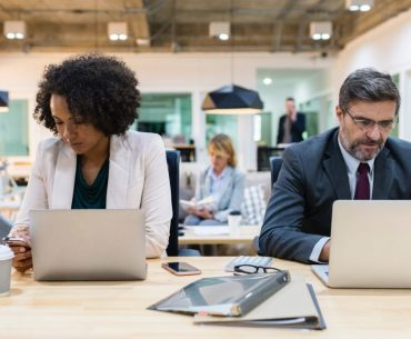 Homem e mulher trabalhando com computador e celular