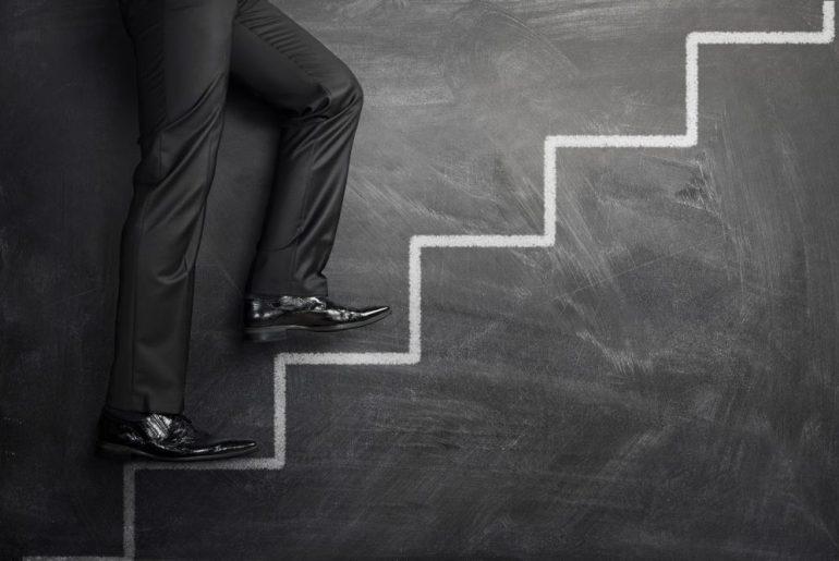 Empresário subindo escada com por conta da expansão de sua marca