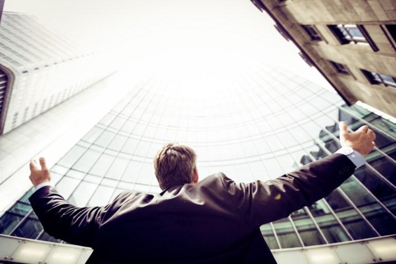 Homem de braços abertos olhando para o céu em meio a vários prédios