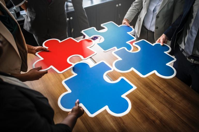 essoas segurando peças de um quebra-cabeça