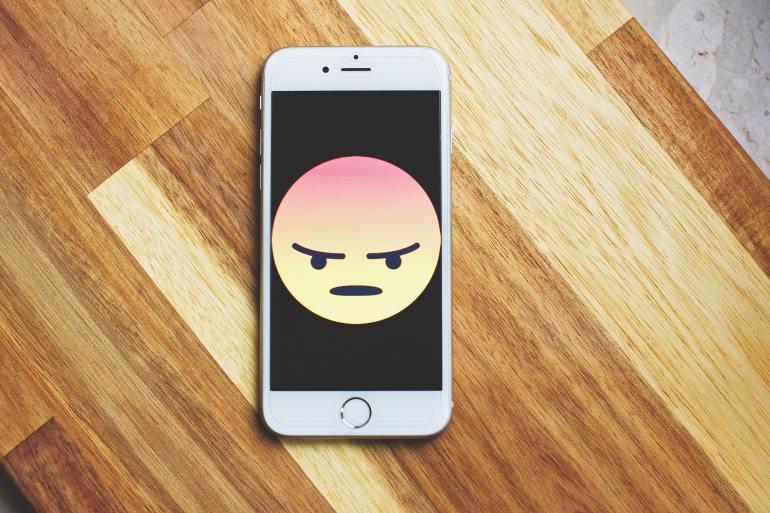 celular com ícone de emoji bravo na tela