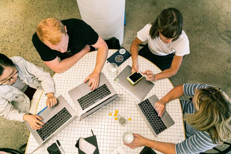 Pessoas reunidas usando notebook