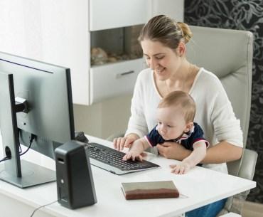 Mãe fazendo home office com filho no colo