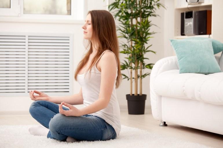 Mulher meditando no tapete de casa
