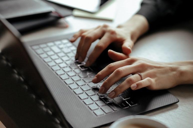 Mãos femininas digitando em laptop.