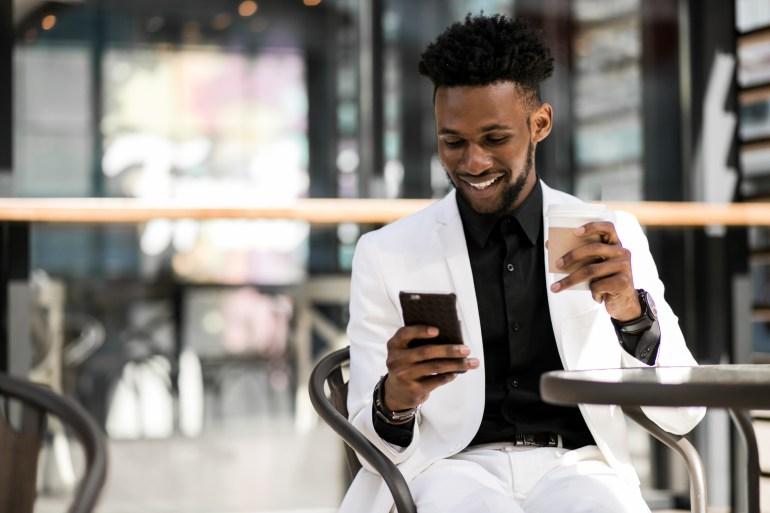 Homem sorridente tomando café com celular em mãos, avaliando estabelecimento no Google Meu Negócio.