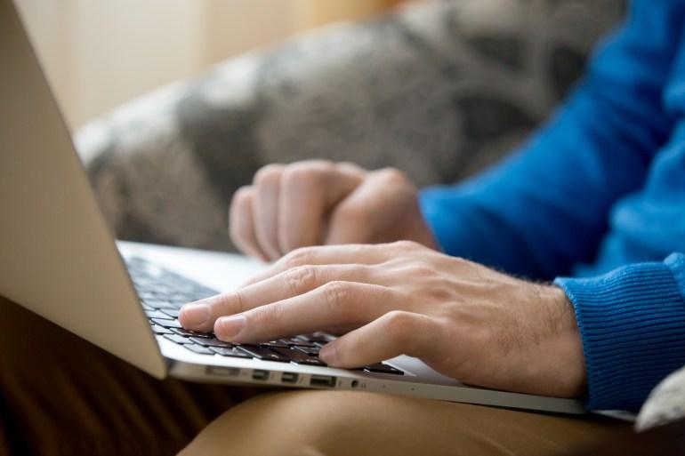 Mãos masculinas sobre laptop.