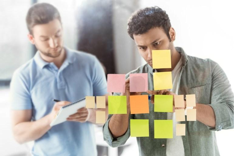 Colaboradores em reunião de brainstorm, colocando post-it na parede