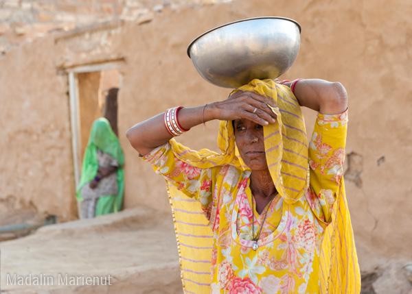 O femeie cara apa spre casa. Zilnic localnicii transporta pe jos apa si de 3 ori pe zi de la izvoare situate la 2-3 km de casa. Desertul THAR.