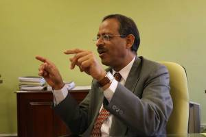 Anil Swarup explaning something with both hands pointing toward audience out of frame